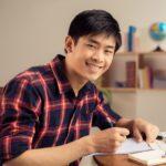 Portrait,Of,Cheerful,Asian,Student,Doing,Homework